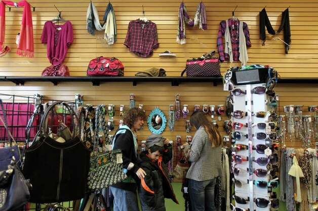 Customers browse the accessories at Plato's Closet at North Park Mall, Monday, January 16, 2012. The franchise buys gently used merchandise that would appeal to the teen to twenty-something demographic and sells them at about 70% of retail cost, paying sellers 35% of their floor price. Photo: JENNIFER WHITNEY, Special To The Express-News / special to the Express-News