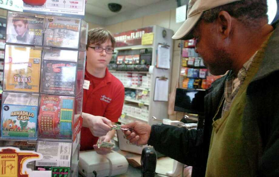 Jeremiah Goad sells a scratch-off ticket to Edgar Johnson at MB Express in Beaumont. Participation in Texas Lottery games rose to 40 percent in 2011, up 7 percentage points from the previous year. Photo: Beaumont Enterprise, Tammy McKinley