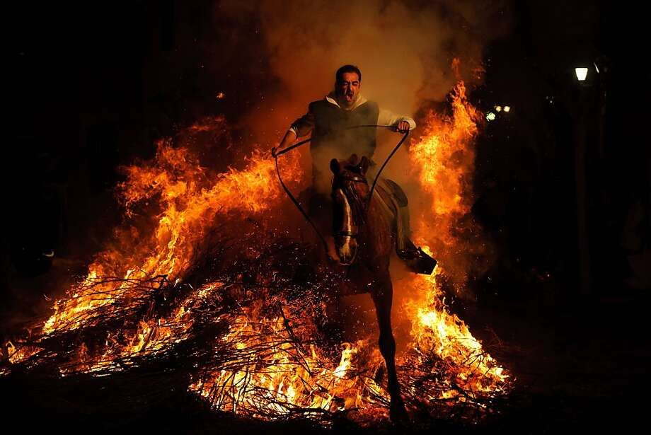 In Spain, riding through flames is 'good' for the horse:A celebrant jumps his mount through a bonfire in San Bartolome de Pinares, Spain, in honor of Saint Anthony, the patron saint of animals. The tradition, which dates back 500 years, is meant to purify horses with the smoke and protect them in the year to come. Photo: Daniel Ochoa De Olza, Associated Press