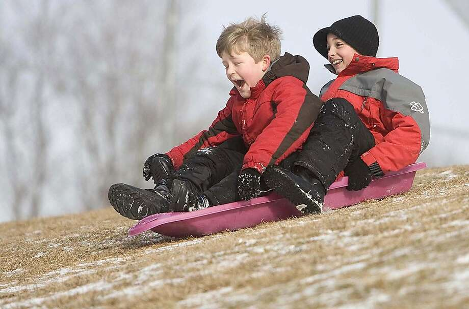 Whee! We're not moving!Andrew Carrington (left) and Stevan Jelic are determined to go sledding on a quarter inch of snow in Oneonta, N.Y. Photo: Benjamin Patton, Associated Press