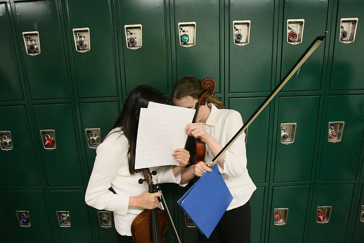 Two members of the All-City Concert Orchestra share some gossip while waiting to go onstage and preform at the All-City Music Festival on Saturday night at Lowell High School. All-City brings together the best orchestra and band musicians from the middle and high schools of the SFUSD. (Laura Morton/Special to the Chronicle)