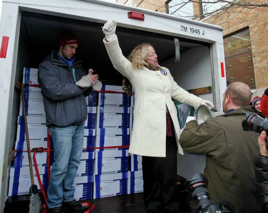 Julie Wells of United Wisconsin celebrates in the back of a moving van Tuesday, Jan. 17, 2012, in Madison, Wis., that contains about 1 million signatures to recall Gov. Scott Walker. (AP Photo/Andy Manis) Photo: Andy Manis