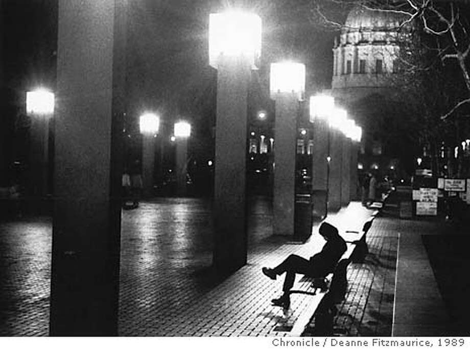 A homeless man sits motionless for hours on a bench in U.N. Plaza with City Hall in the background on March 3, 1989. He said he was going to Hamilton Shelter later on to sleep. CHRONICLE PHOTO BY DEANNE FITZMAURICE/1989