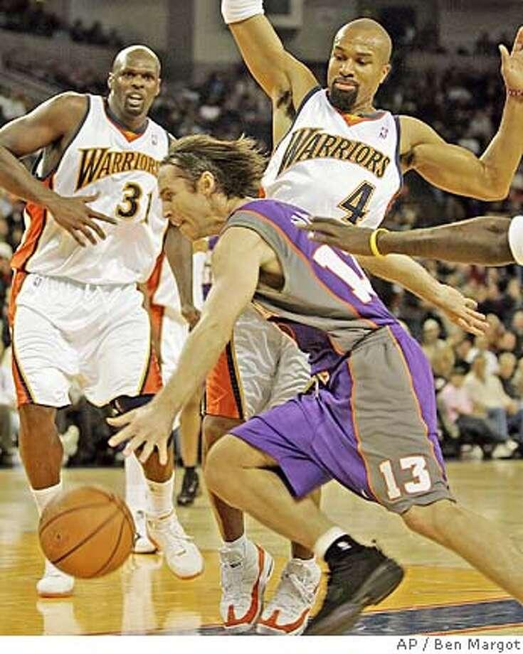 Phoenix Suns' Steve Nash (13) drives past Golden State Warriors' Derek Fisher (40) and Adonal Foyle (31) in the first half, Wednesday, Dec. 7, 2005, in Oakland, Calif. (AP Photo/Ben Margot) EFE OUT Photo: BEN MARGOT
