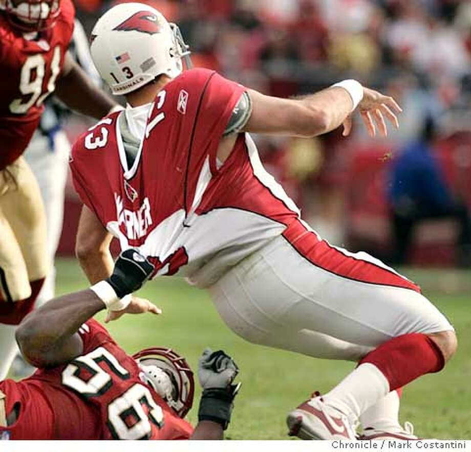 49ers linebacker Brandon Moore(56) tackles Cardinals QB Kurt Wamer iin the first half.  49ers v. Arizona Cardinals as Monster Park.  Event on 12/4/05 in San Francisco  Photo: Mark Costantini /San Francisco Chronicle Photo: MARK COSTANTINI