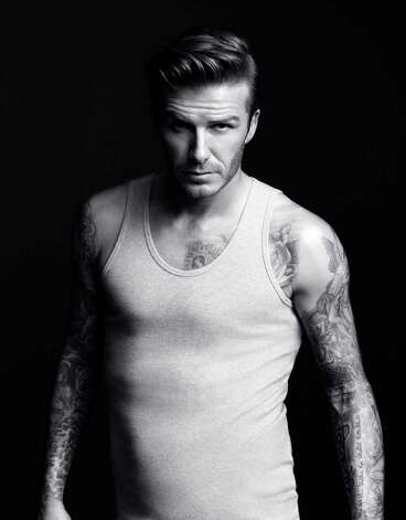 David Beckham shows off his tattoos in a gray ribbed tank top. The garment is among nine items in the line that will debut during a Super Bowl ad. Photo: H&M, Courtesy