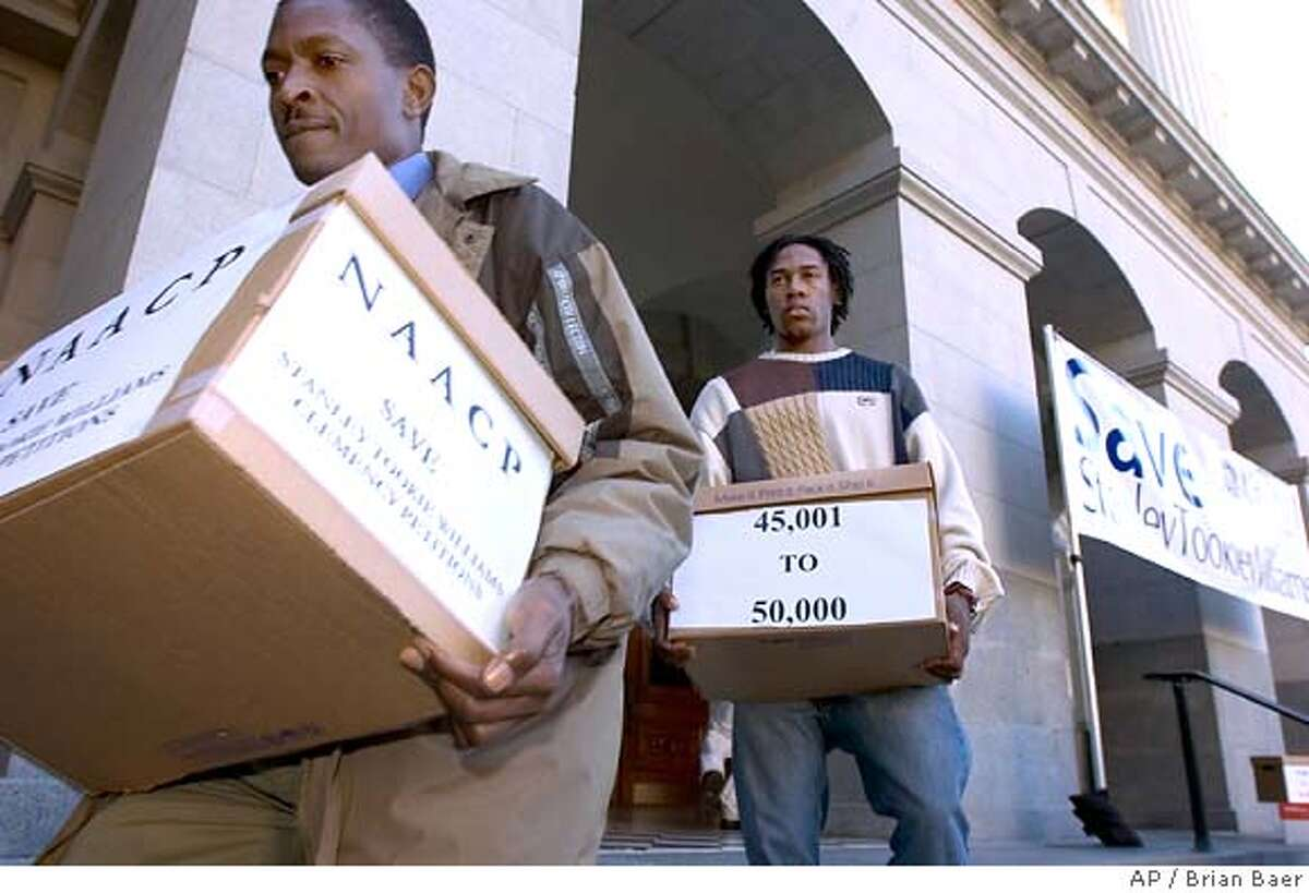 Ariemba Momanyi , left and Vincent Payne, carry some of the thousands of signed clemency petitions the NAACP delivered to California Gov. Arnold Schwarzenegger in Sacramento, Calif., part of an attempt to save death row inmate Stanley Tookie Williams, Tuesday, Dec. 6, 2005. Williams, co-founder of the Crips gang in Los Angeles, was convicted of killing four people in two 1979 robberies. He is scheduled to be executed Dec. 13. (AP Photo/The Sacramento Bee, Brian Baer) ** MANDATORY CREDIT **