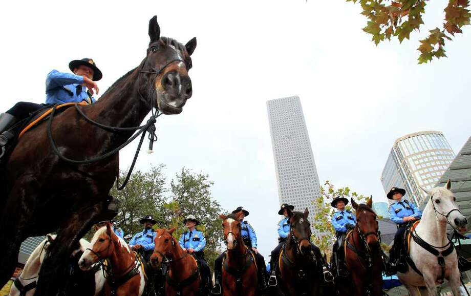Lt. Randall Wallace, left, head of the Houston Police Department's Mounted Patrol unit, rides the first horse sponsored under its Adopt-a-Horse Program on Tuesday in Market Square downtown Tuesday. Photo: Johnny Hanson / © 2012  Houston Chronicle