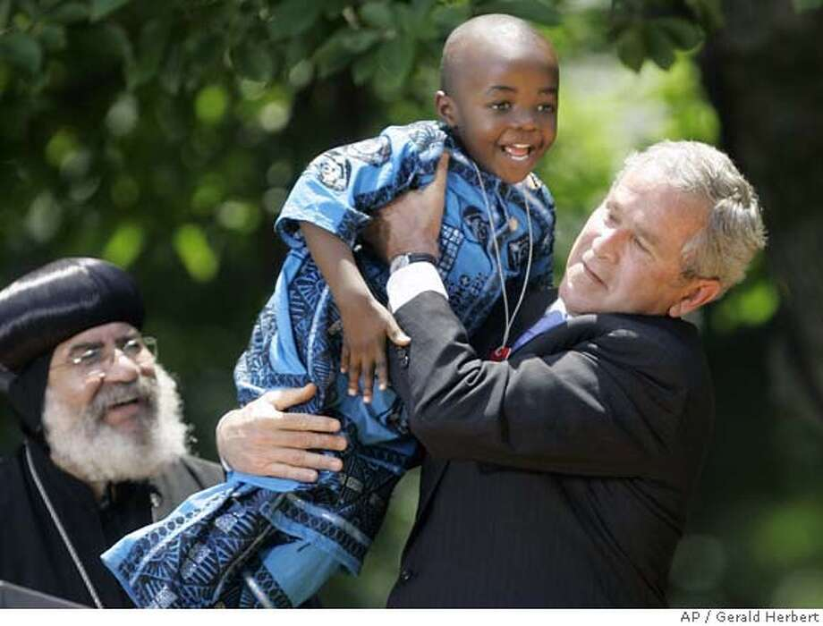 ** CORRECTS SPELLING TO MOSIMA ** President Bush, right, picks up Baron Mosima Loyiso Tantoh, 4, after making remarks on the President's Emergency Plan For AIDS Relief, Wednesday, May 30, 2007, in the Rose Garden of the White House in Washington, Wednesday, May 30, 2007. At left is Bishop Paul Yowakim. (AP Photo/Gerald Herbert) RETRANSMISSION OF WHGH101 WITH ALTERNATE CROP ** CORRECTS SPELLING TO MOSIMA ** Photo: Gerald Herbert