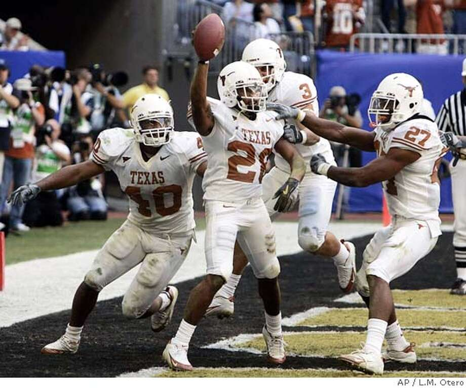 Texas Brandon Foster (28) celebrates his third quarter touchdown after recovering a Colorado blocked punt in the end zone with teammates Robert Killebrew (40) Karim Mekjer (3) and Michael Griffin (27) in the Big 12 championship game in Houston, Saturday, Dec.3, 2005. (AP Photo/L.M. Otero) Photo: L.M. OTERO