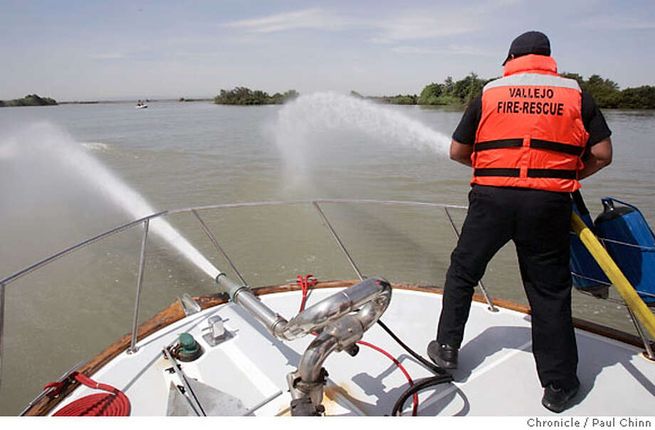 Vallejo firefighter Bruce Phillips sprays water towards a whale as marine biologists attempted to coax two wayward humpback whales back towards the Pacific Ocean using a fireboat from the Vallejo Fire Department in Rio Vista, Calif. on Friday, May 25, 2007. The whales responded to the spray from the boat initially but, fearing they may get used to the activity, the operation was suspended after about an hour and may try again using additional resources. PAUL CHINN/The Chronicle  **Bruce Phillips Photo: PAUL CHINN
