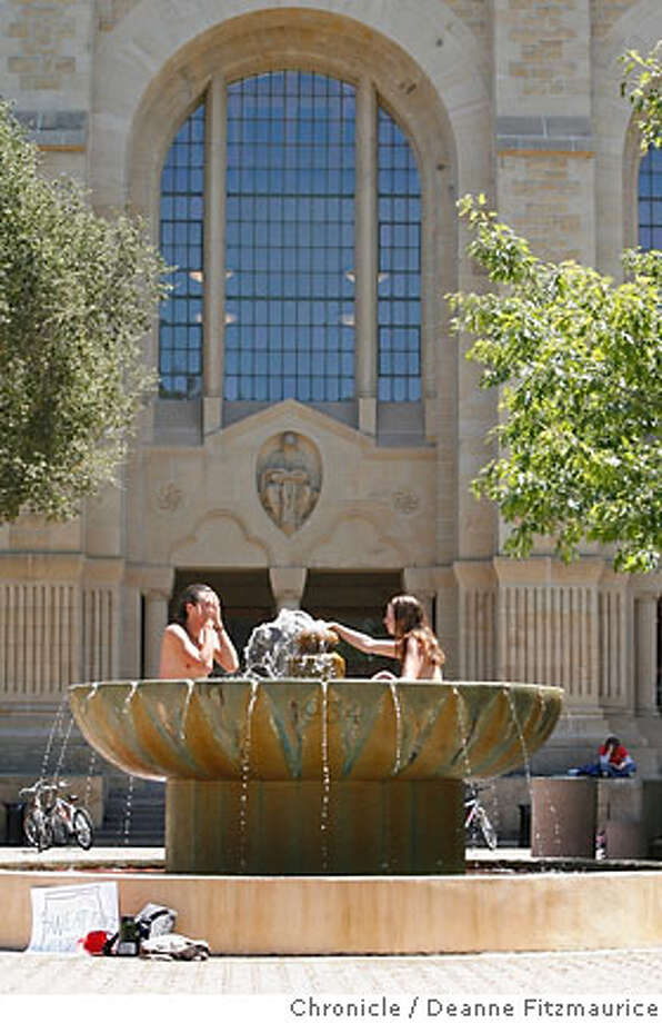 Christine Hoffmann (cq), wearing no top, and Bradley Heinz (cq) wearing no clothes, walk to take a dip in a fountain on campus to cool off during a break in the rally. Stanford University students, some naked, hold a rally outside of the University President John Hennessy's office on campus to demand the University end sweatshop conditions in factories making its apparel. Chronicle Photographed in Stanford on 5/22/07. Deanne Fitzmaurice / The Chronicle Photo: Deanne Fitzmaurice