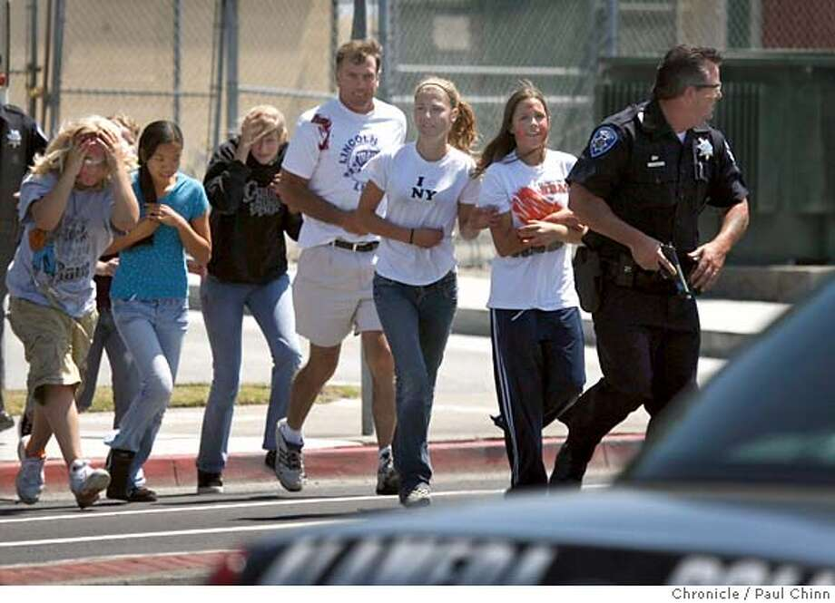 "A police officer leads ""victims"" to safety during the Alameda Police Department's safe school training exercise at Lincoln Middle School in Alameda, Calif. on Tuesday, May 22, 2007. The scenario, in the planning stages for the past 18 months, included three armed assailants that fired several gunshots injuring several students and taking up to 45 hostages. PAUL CHINN/The Chronicle Photo: PAUL CHINN"