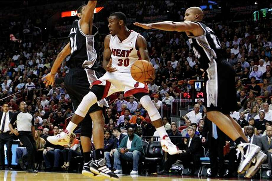 Miami Heat's Norris Cole (30) looks to pass the ball as San Antonio Spurs' Tim Duncan (21) and Richard Jefferson (24) defend during the first half of an NBA basketball game, Tuesday, Jan. 17, 2012, in Miami. (AP Photo/Lynne Sladky) Photo: Associated Press