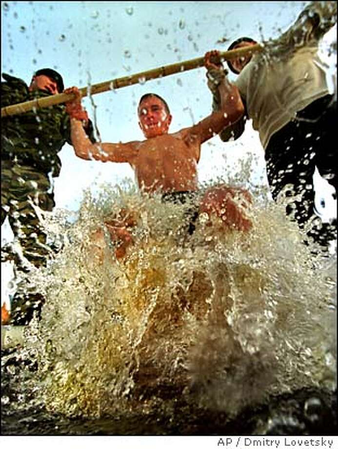 Two men, Russian Orthodox believers, help a man to plunge into consecrated ice cold water in observation of Orthodox Epiphany tradition in the town of Sestroretsk, 30 km (19 miles) west of St. Petersburg, Russia, Wednesday, Jan. 19, 2005. (AP Photo/Dmitry Lovetsky Photo: DMITRY LOVETSKY