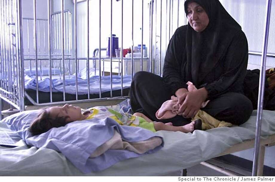 Tahar Nahdiin lay on his back as his mother Hassna, 35, looks over him in the Ibn Al-Baladi Pediatric Hospital in the Shi'a slum Sadr City in east Baghdad, Iraq, on May 12, 2007. Nahdin, 1, who is is suffering from malnutrition and dehydration, has no access to antibiotics and intravenous solutions that could help prolong his life due to the hospital's shortages and her parents poverty. The rate of mortality among children younger than 5 in Iraq shot up 150 percent between 1990 and 2005, this according to a report recently released by the U.S.-based humanitarian aid group Save the Children. In 2005 across Iraq 122,000 children � or one in eight � died before the age of 5, according to the report. JAMES PALMER / SPECIAL TO THE CHRONICLE NO MAGS, NO SALES, NO TV Photo: James Palmer