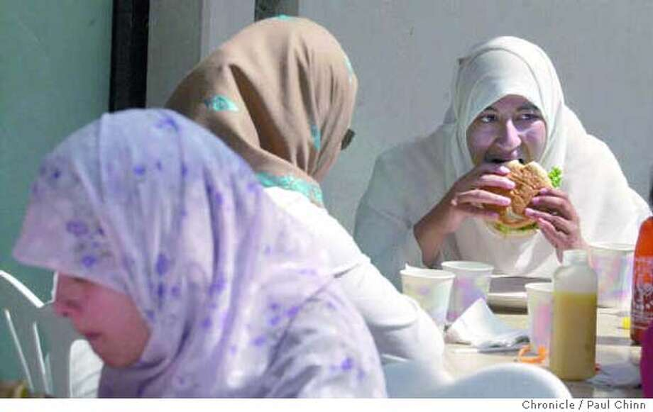 Arefa Vohra (right) bites into hamburger made with halal ground beef at Julie's Healthy Cafe in Berkeley. Chronicle photo by Paul Chinn