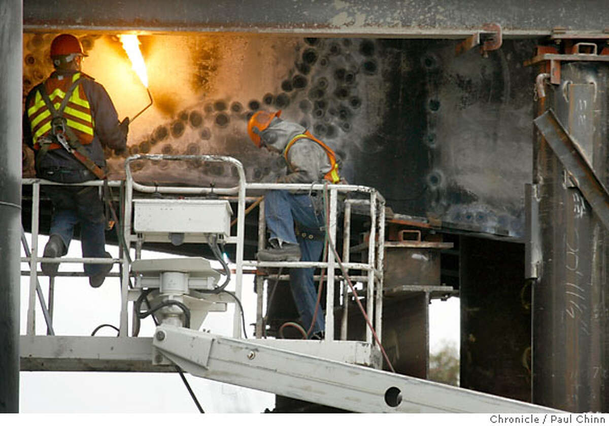 A welder adjusts his torch below the I-880 ramp while construction crews continue to rebuild the damaged sections of the MacArthur Maze in Oakland, Calif. on Tuesday, May 15, 2007 after a fiery gas tanker explosion closed two of the ramps two weekends ago. The I-880 ramp will be closed later this evening so contractors can lift a huge concrete section into place for the I-580 ramp replacement. PAUL CHINN/The Chronicle