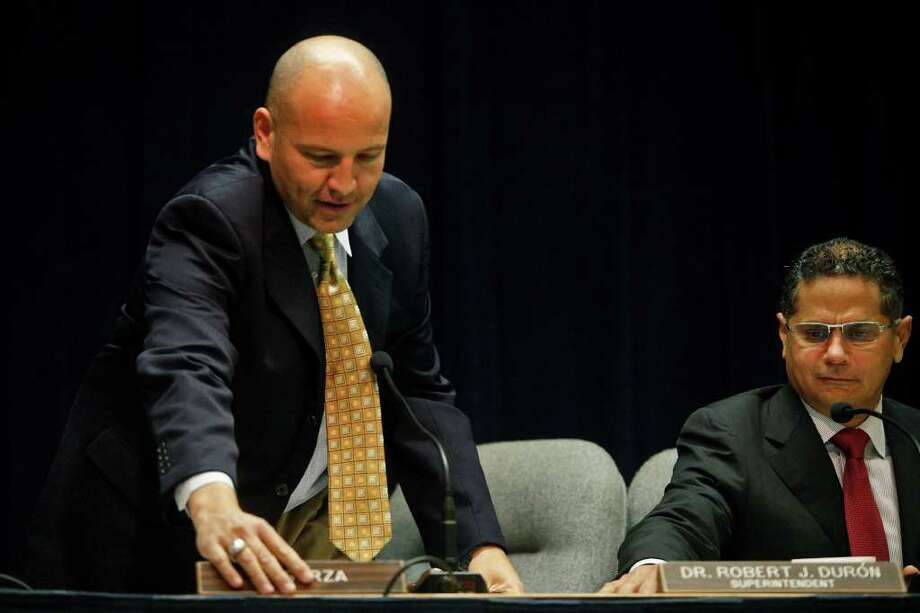 New SAISD board President Ed Garza (left) puts his nameplate in place as he takes his seat next to district Superintendent Robert Durón. Photo: San Antonio Express-News, Lisa Krantz / @2012 SAN ANTONIO EXPRESS-NEWS