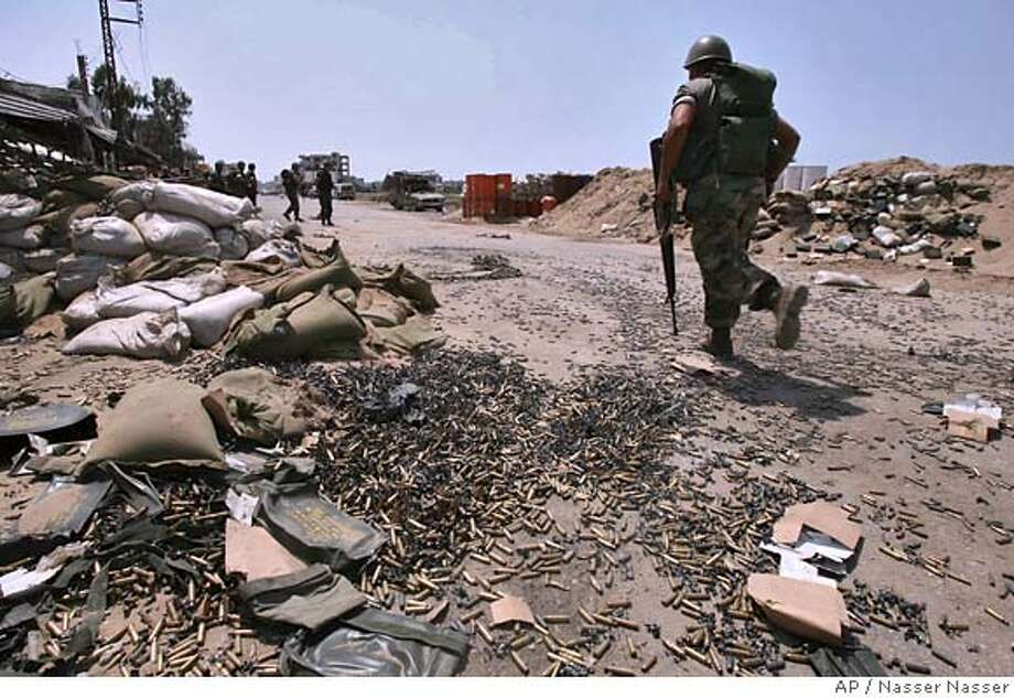 A soldier runs over empty rounds that cover the road near a Lebanese army position at the entrance of the Palestinian refugee camp of Nahr el-Bared in the northern city of Tripoli, Lebanon Tuesday, May 22, 2007. Artillery and machine gun fire echoed around a crowded Palestinian refugee camp for a third straight day Tuesday, while angry Palestinians burned car tires in two other camps in an ominous sign that the trouble could spread across Lebanon. (AP Photo/Nasser Nasser) Photo: NASSER NASSER