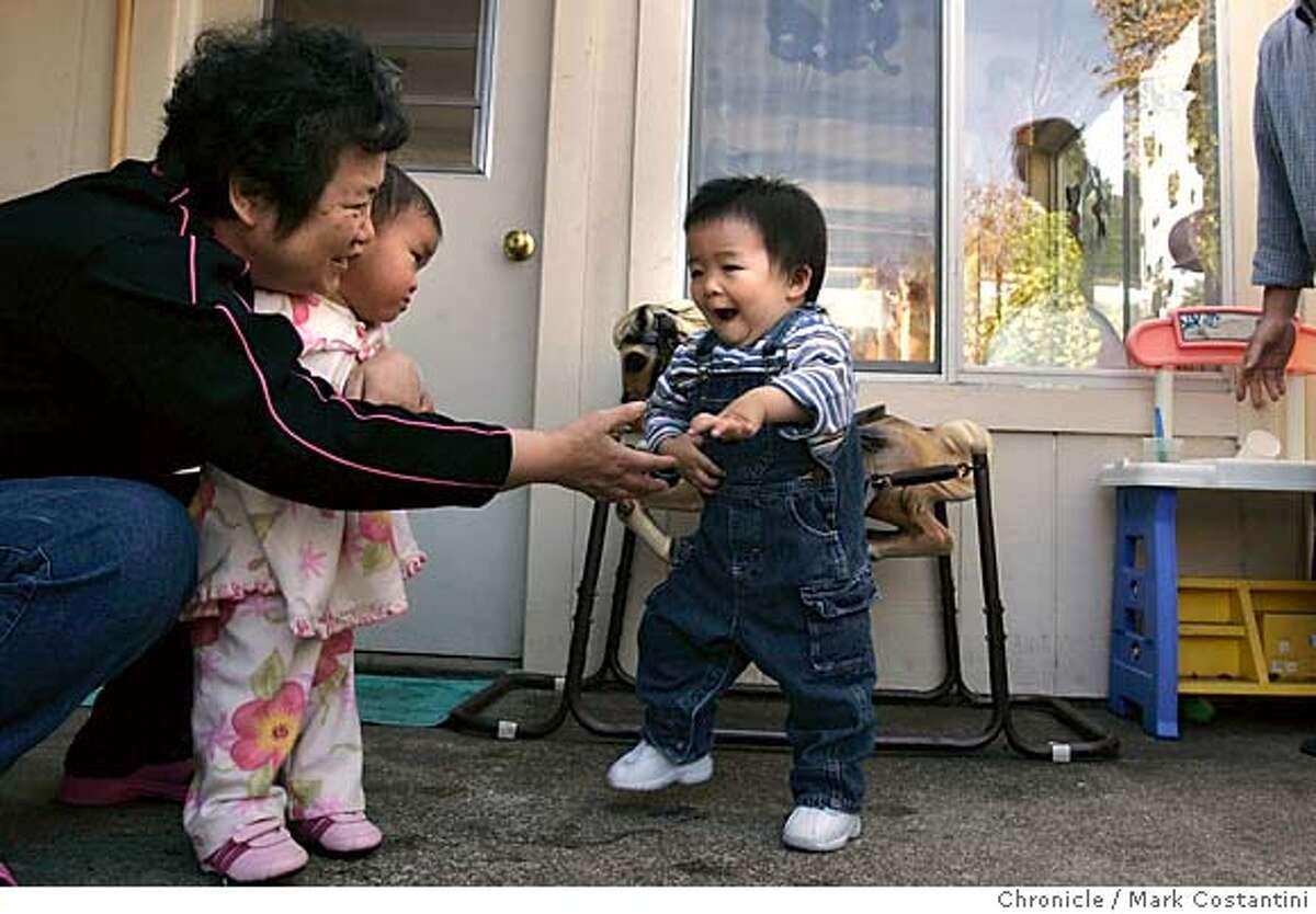 """LANGUAGENANNY -- Ada Chow(picured here at with children she takes care of, the little boy walking toward her smiles as he walks toward Ada--he is recovering from a major illness) serves as a """"language nanny"""" to about six kids of Chinese descent, some of them adoptees. The kids are dropped off by 9 am. She plays with them, serves them lunch and generally provides socialization skill training. Event on 11/18/05 in OAKLAND. Photo:San Francisco Chronicle, Mark Costantini"""