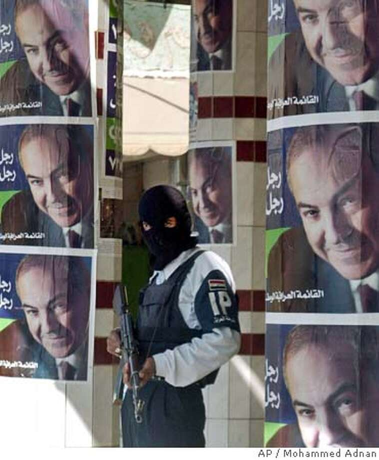 An hooded Iraqi policeman stands near electoral posters for former Iraqi Prime Minister Ayad Allawi, reading, 'Allawi the man for this stage, the man of the future. Iraqi National Iraqi list', posted for the Dec. 15 parliamentary elections, in Baqouba, Iraq, Saturday, Nov. 26, 2005. (AP Photo/Mohammed Adnan) Photo: MOHAMMED ADNAN