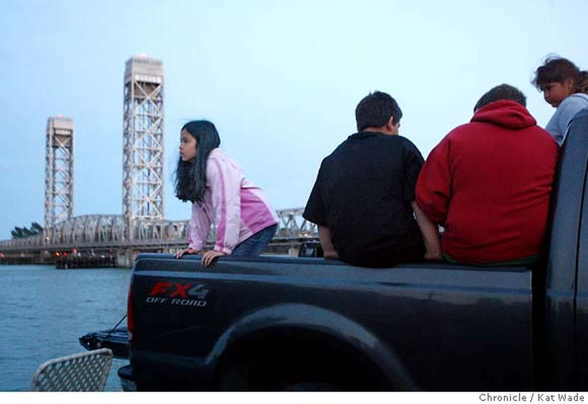 Reminiscent of an old drive in movie, Annette Josol, 10, Devin DeLaRosa, 9, Austin DeLaRosa, 11, and Samantha Mitchell, 10 all of Rio Vista sit in the back of a pickup at the edge of the Sacramento River in hopes of getting a glimpse of the two injured humpback whales who began to swim towards the ocean from the Sacramento River at the port of Sacramento at approximately 2pm today. The whales had not reached Rio Vista by dark at around 8:30 p.m. Kat Wade/The Chronicle