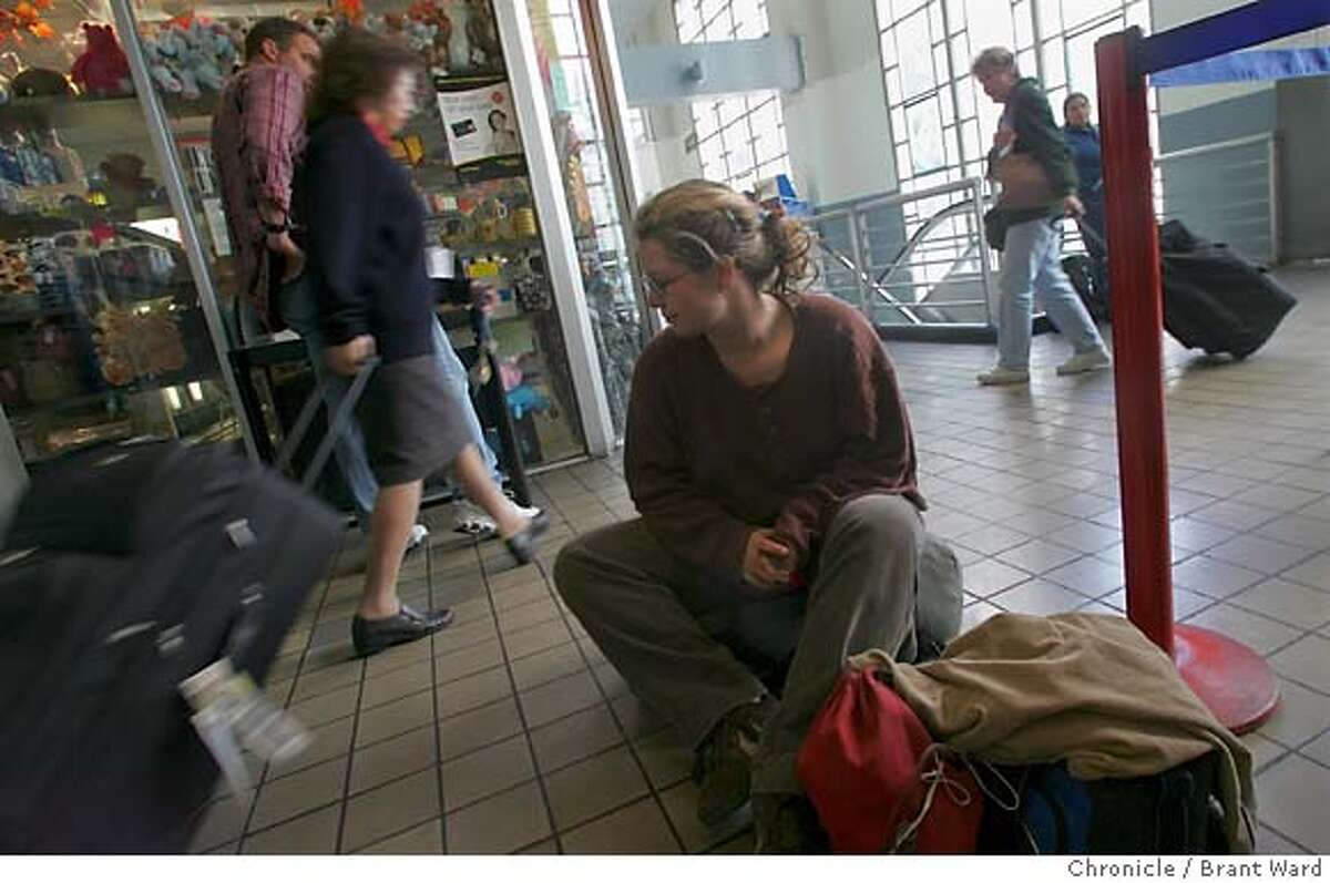 Johnye Williams, a homeless girl, sits on the ground at the San Francisco Greyhound station waiting for her bus. In background Jon McMahon,a SFPD officer involved with the return-to-residence program, makes a call. A San Francisco program to help the homeless return home or to a loved one has had great success. Several hundred homeless have left the city on a Greyhound bus thanks to the program. 11/9/05