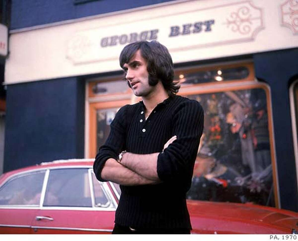 ** FILE ** George Best the former Northern Ireland and Manchester United soccer star is seen in this January 1970 file photo standing outside his store in Manchester, England. Best, the dazzling soccer icon of the 1960s and 70s who reveled in a hard-drinking playboy lifestyle, died Friday Nov. 25, 2005 after decades of alcohol abuse, hospital officials said. He was 59. (AP Photo/PA/file) ** UNITED KINGDOM OUT NO ARCHIVE **
