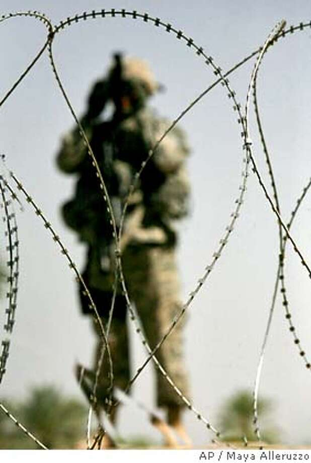 A soldier attached to Delta Company, 4th Battalion, 31st Infantry Regiment, 2nd Brigade, 10th Mountain Division is seen through newly-installed concertina wire as he eyes the road during a patrol eight days after a May 12 attack that left four U.S. soldiers and an Iraqi soldier dead and three comrades missing in Quarghuli village, near Youssifiyah, 12 miles (20 kilometers) south of Baghdad, Iraq Sunday, May 20, 2007. (AP Photo/Maya Alleruzzo) Photo: MAYA ALLERUZZO