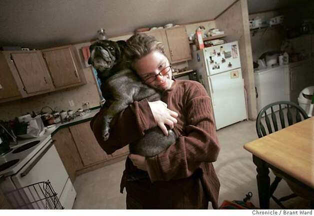 Just after walking in her house, Johnye Williams greets one of the family pugs in the kitchen.  Johnye Williams, a homeless girl living in San Francisco, is sent home on a bus as part of the Homeward Bound program. Homeless people are given Greyhound bus tickets to return home, providing they are returning to family or loved ones.  11/10/05 Photo: Brant Ward