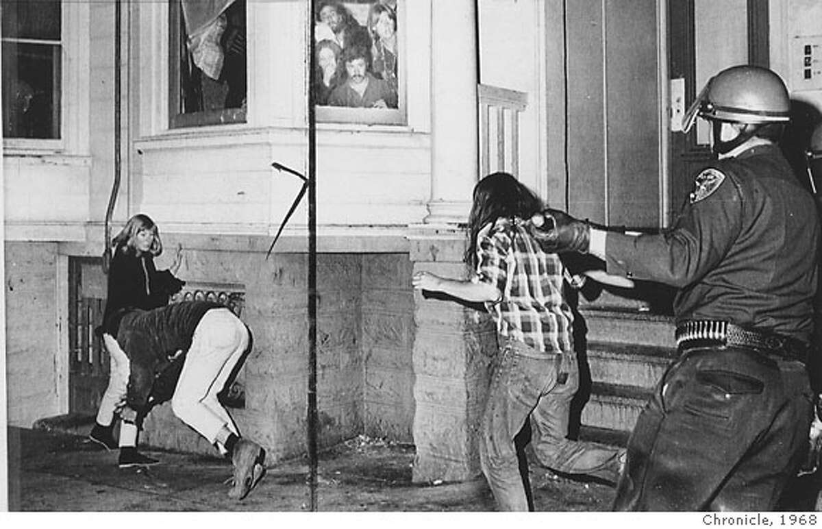 San Francisco July 19, 1968 Pursued, Pursuers and Spectators--A group of hippies stare from the window of their pad as another trips and falls to the ground while being pursued by the police during a third night of violence and shooting in San Francisco's famed Haight-Ashbury district. At least one person was shot, one injured and a number of fire bombs thrown last night.