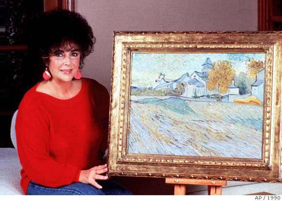"** FILE ** Actress Elizabeth Taylor, displays her Vincent Van Gogh painting, ""View of the Asylum of Saint-Rmy,"" at her Los Angeles home in this Nov. 5, 1990, file photo. Canadian lawyer Andrew J. Orkin and three family members say the Nazis took the masterpiece from Orkin's German great-grandmother, Margarete Mauthner, during World War II, and they are demanding that Taylor return the artwork to them. Taylor is seeking a court declaration that she is the rightful owner of the painting. (AP Photo/HO) Ran on: 07-04-2004  Elizabeth Taylor displays her Vincent van Gogh painting, which another family claims Nazis took from their great-grandmother."
