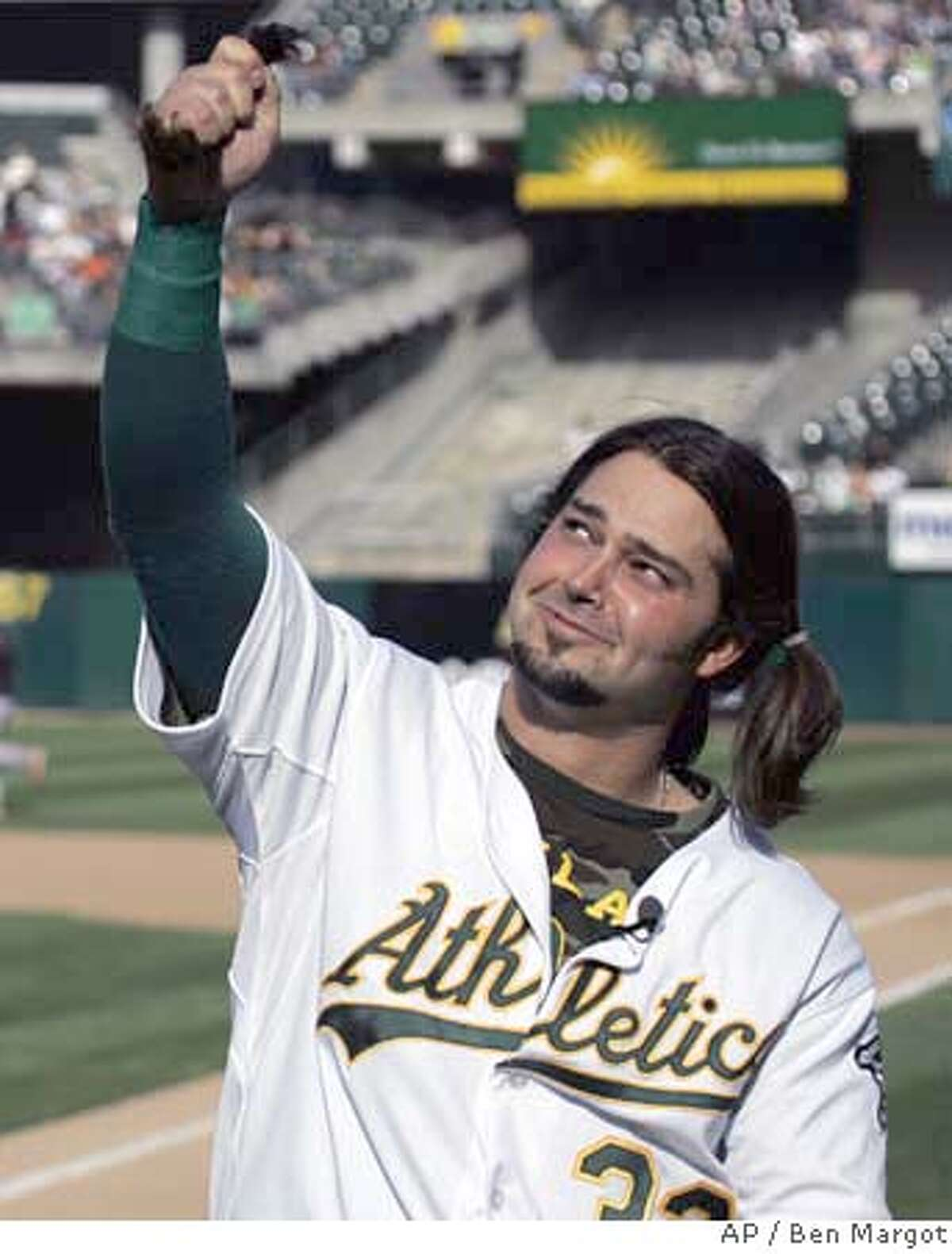 Oakland Athletics center fielder Nick Swisher holds his ponytail of hair cut at home plate by his father, former major league baseball player Steve Swisher, prior to the baseball game with the San Francisco Giants Saturday, May 19, 2007, in Oakland, Calif. Swisher had not cut his hair since the beginning of spring training, with the intention of donating his locks for a wig to be made for a woman with cancer, in honor of his grandmother who died of the illness. (AP Photo/Ben Margot)
