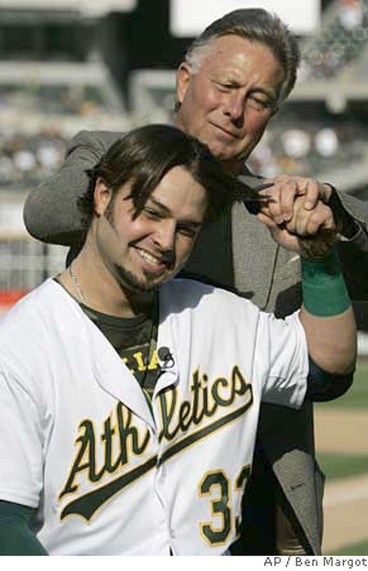 Oakland Athletics center fielder Nick Swisher, bottom, has his ponytail cut by his father, former major league baseball player Steve Swisher, prior to the baseball game with the San Francisco Giants, Saturday, May 19, 2007, in Oakland, Calif. Swisher had not cut his hair since the beginning of spring training, with the intention of donating his locks for a wig to be made for a woman with cancer, in honor of his grandmother who died of the illness. (AP Photo/Ben Margot)