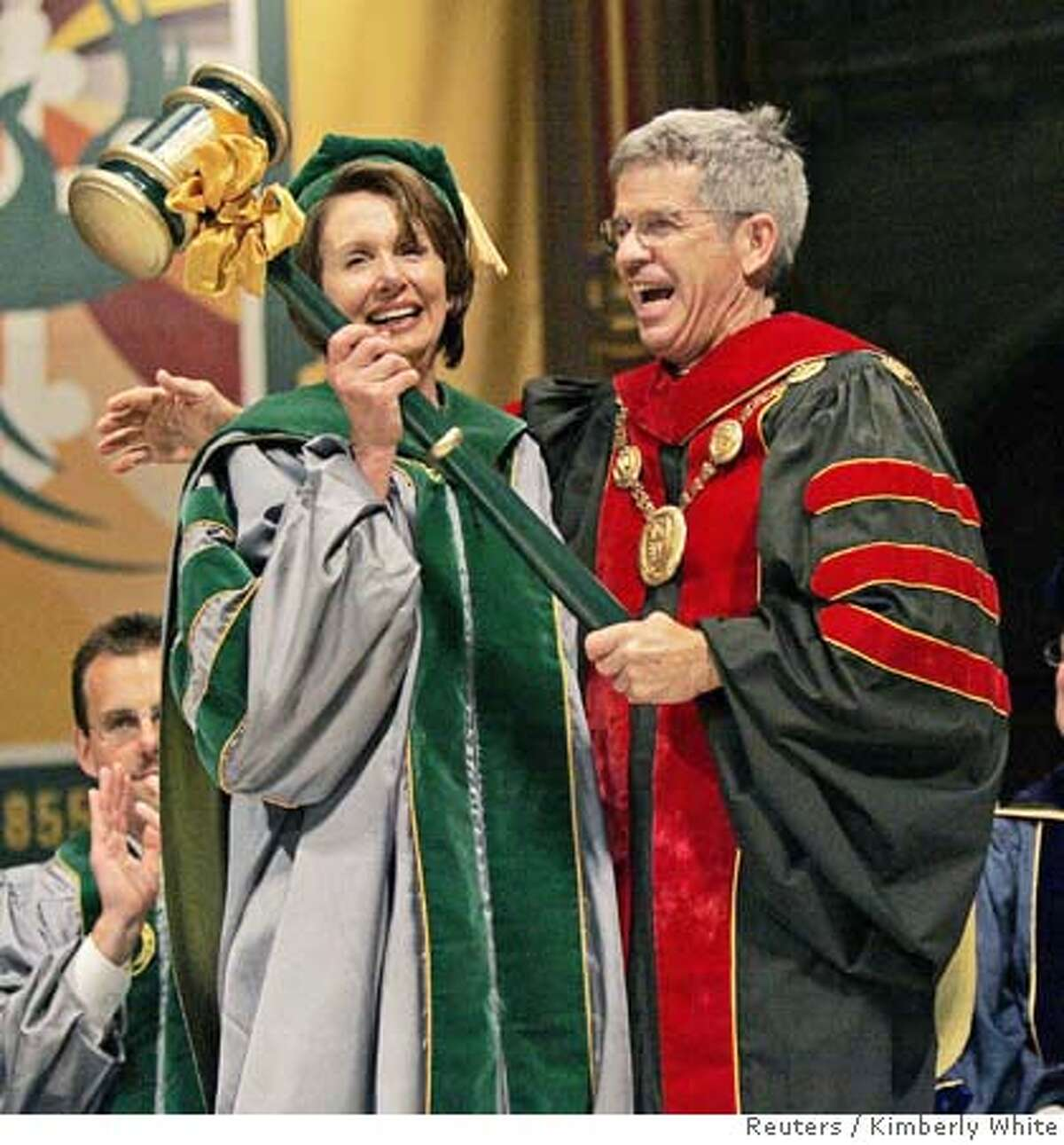 Speaker of the House Nancy Pelosi (D-CA) (L), is given an oversized gavel as a joke from Stephen Privett, president of the University of San Francisco in San Francisco, California, May 19, 2007. House Speaker Pelosi gave a brief speech to the graduating class of the McLaren College of Business. REUTERS/Kimberly White (UNITED STATES)