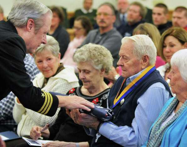 Cdr. Paul Martineau, left, USN Ret., presents an American flag to Robert Stevens of Hoosick Falls during a ceremony Tuesday Jan. 17, 2012, honoring Robert's brother Harold Stevens, a 21-year-old Saratoga Springs man who died in a German POW camp in France near the end of World War II   (John Carl D'Annibale / Times Union) Photo: John Carl D'Annibale / 00016115A