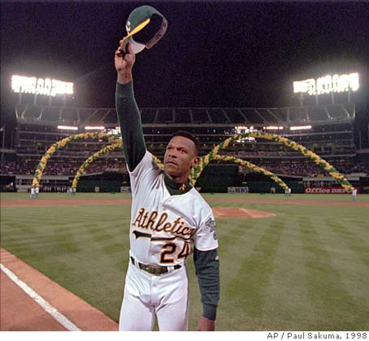 Oakland Athletics left fielder Rickey Henderson waves to the crowd as he is introduced before the game against the Boston Red Sox, Wednesday night, April 1, 1998, at the Oakland (Calif.) Coliseum. (AP Photo/Paul Sakuma)