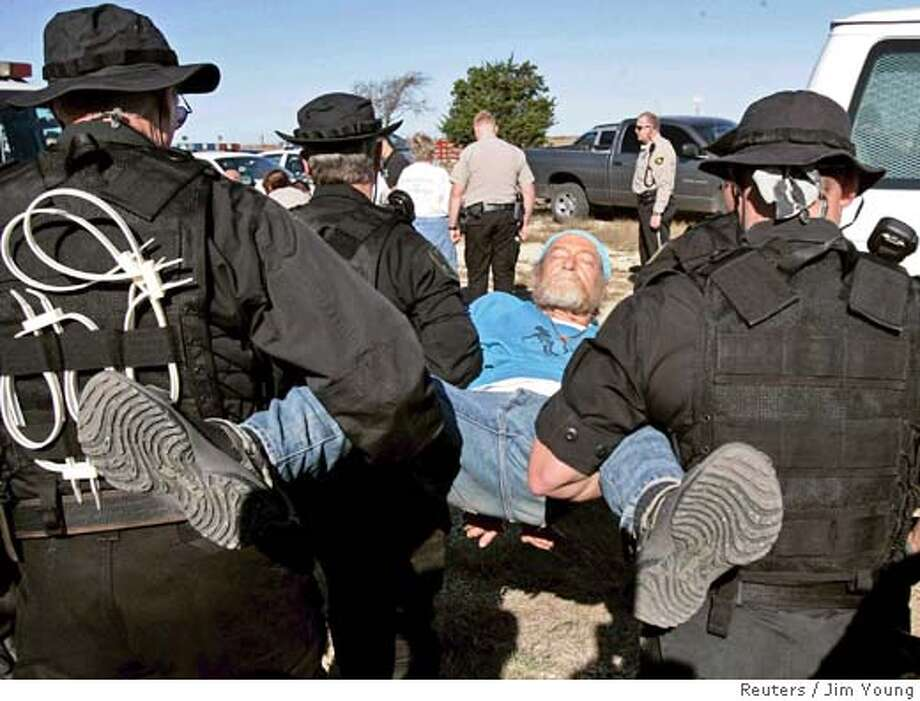 An anti-war protester is carried away by McLennan County sheriff deputies after being arrested near U.S. President George W. Bush's ranch in Crawford, Texas, November 23, 2005. A dozen people were arrested for criminal trespassing as they demonstrated against the president's stance on troops in Iraq. REUTERS/Jim Young Ran on: 11-24-2005  An anti-war protester is carried away by McLennan County sheriff's deputies after being arrested. Photo: JIM YOUNG