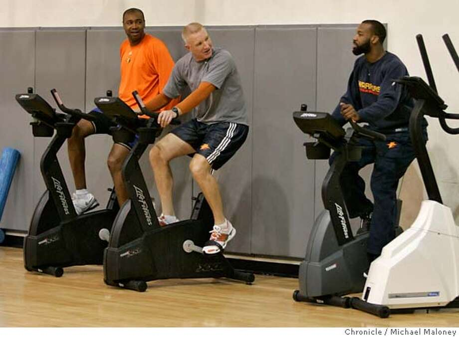 While warming up on the stationary cycle, Golden State Warriors Baron Davis (right) talks with Chris Mullin, Executive Vice President of Basketball Operations and at far left, Rod Higgins (General Manager).  The Golden State Warriors hold a press conference and short workout at their practice facility in downtown Oakland, CA on April 26, 2007.  Photo by Michael Maloney / San Francisco Chronicle *** Baron Davis, Chris Mullin, Rod Higgins MANDATORY CREDIT FOR PHOTOG AND SF CHRONICLE/NO SALES-MAGS OUT Photo: Michael Maloney