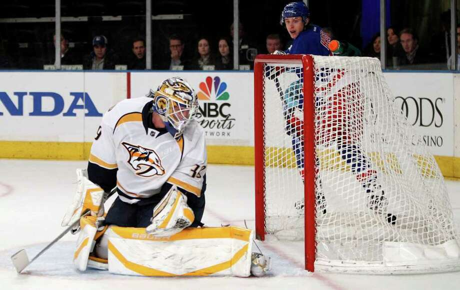 New York Rangers left wing Carl Hagelin, rear, watches as John Mitchell's goal slips in behind Nashville Predators goalie Anders Lindback (39) in the second period of an NHL hockey game at Madison Square Garden in New York, Tuesday, Jan. 17, 2012.  (AP Photo/Kathy Willens) Photo: Kathy Willens