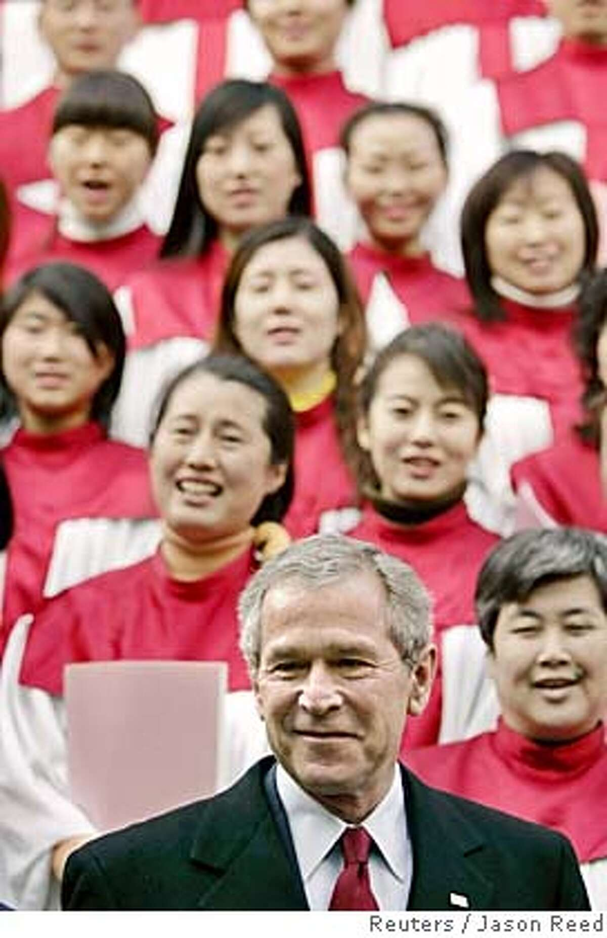 U.S. President George W. Bush poses with members of a Chinese church choir after attending a Sunday church service in Beijing, November 20, 2005. Bush plans to press Chinese President Hu Jintao on Sunday to rein in China's ballooning trade surplus in talks he said would be frank. Bush is in China on a two-day visit. REUTERS/Jason Reed 0