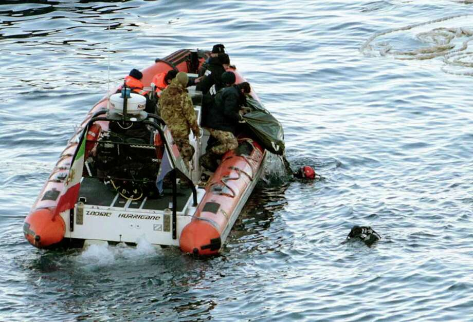 Italian naval divers recover a body from the cruise ship Costa Concordia, Tuesday, Jan. 17, 2012. Italian media say five bodies have been found aboard a cruise ship capsized off the coast of Tuscany, raising the official death toll to 11. Teams have been searching the ship for passengers and crew missing since the Costa Concordia struck rocks Friday evening and capsized. Rescuers exploded four holes in the hull of the ship earlier Tuesday to gain easier access to areas that had not yet been searched. (AP Photo/Gregorio Borgia) Photo: Gregorio Borgia / AP