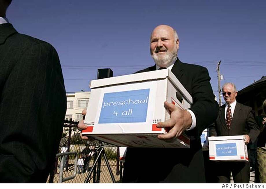 "Hollywood actor and director Rob Reiner, center, carries boxes at a news conference at a playground in San Francisco, Thursday, Nov. 17, 2005 with state business leaders from around California of some one million ballot measures that were signed. Reiner, a longtime supporter of early education programs, said Thursday that his group has collected enough signatures to get a measure on the June 2006 ballot asking Californians to raise the tax rate for high-income earners and provide universal preschool. He announced that he has collected one million signatures for his initiative ""Preschool for All."" (AP Photo/Paul Sakuma) Photo: PAUL SAKUMA"
