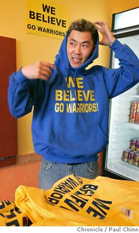 "Golden State Warriors fan Paul Wong slips on a sweatshirt behind a stack of the ""We Believe"" t-shirts he created at his Hawaiian Drive Inn (cq) restaurant in Alameda, Calif. on Friday, May 11, 2007. The t-shirts have become a hot commodity among fans after he started wearing the shirt to games since March. Now even the basketball team has been distributing shirts with the slogan on it with Wong's blessing.  PAUL CHINN/The Chronicle  **Paul Wong MANDATORY CREDIT FOR PHOTOGRAPHER AND S.F. CHRONICLE/NO SALES - MAGS OUT Photo: PAUL CHINN"