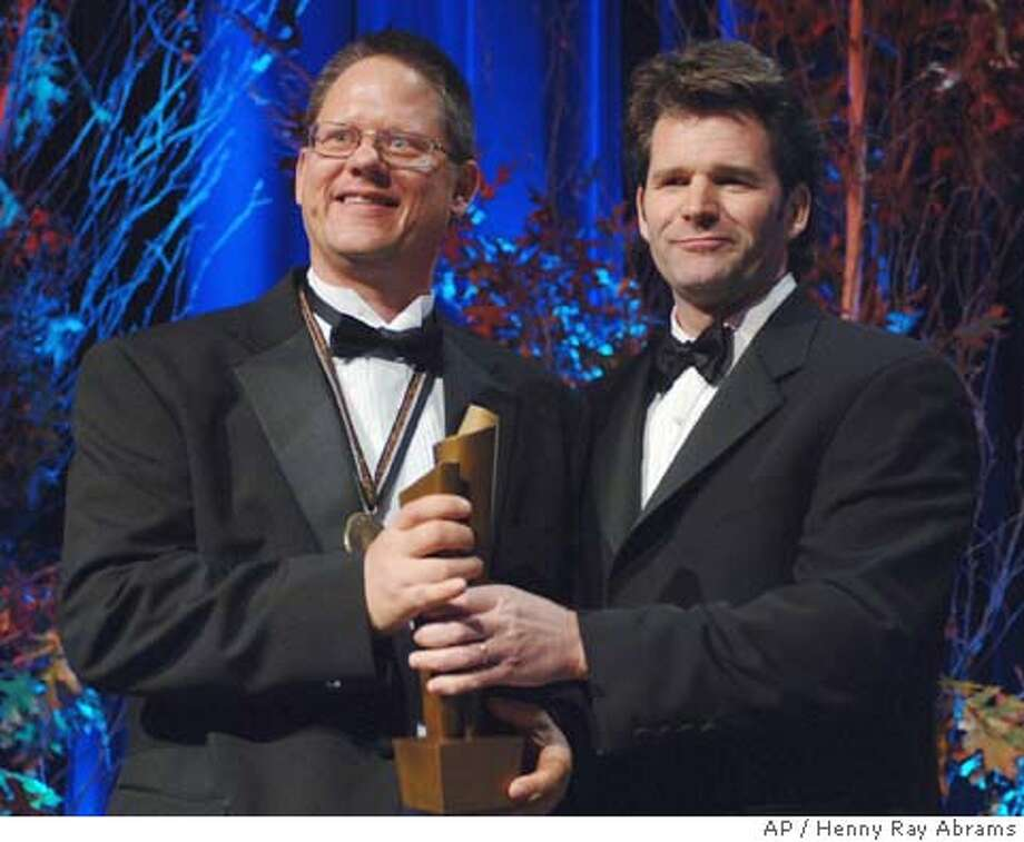 "Author William Vollman, left, accepts the National Book Award for fiction from fellow writer Andre Dubus, right, at the National Book Awards ceremony in New York, Wednesday, Nov. 16, 2005. Vollman won for ""Europe Central,"" a series of intertwined stories about the decisions made by various authoritarian figures in Germany and the Soviet Union in the twentieth century. (AP Photo/Henny Ray Abrams) Photo: HENNY RAY ABRAMS"
