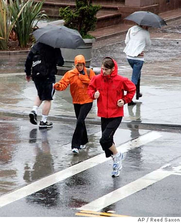 The few pedestrians out and about hurry through rain falling on the Third Street Promenade in Santa Monica, Calif., Friday, April 20, 2007. (AP Photo/Reed Saxon) Photo: Reed Saxon