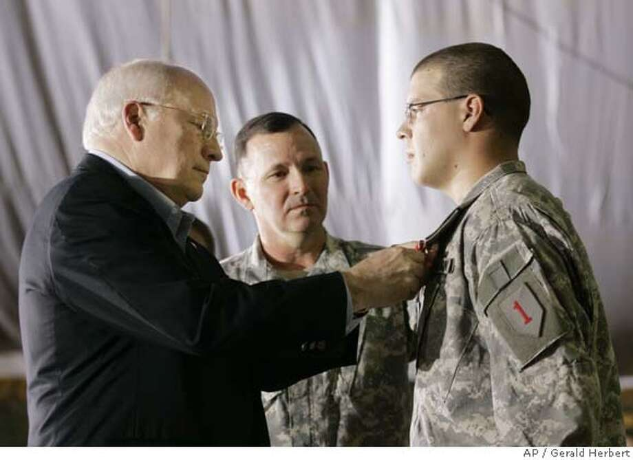Vice President Dick Cheney, left, pins the Bronze Star Medal on Spc. Joshua Sullivan of Company C, 1st Batallion 505th Parachute Infantry Regiment, during a medal ceremony and troop rally at Camp Speicher, Iraq Thursday, May 10, 2007. At center is Maj. Gen. Benjamin Mixon, commander of Multi-National Division North in Iraq. (AP Photo/Gerald Herbert) Photo: Gerald Herbert