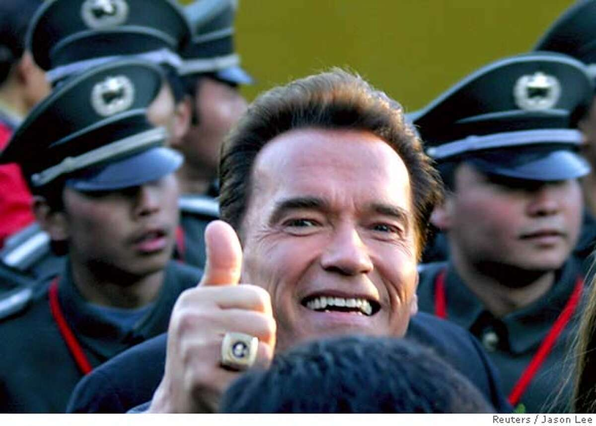 California Governor Arnold Schwarzenegger gestures as he leaves after a ceremony for the Special Olympics at the Millenium Monument in China's capital Beijing November 14, 2005. Schwarzenegger is on a six-day visit in China. REUTERS/Jason Lee 0