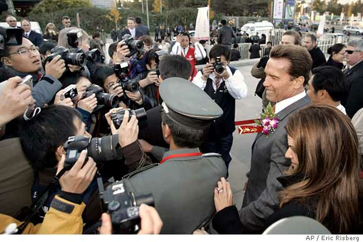 California Governor Arnold Schwarzenegger and First Lady Maria Shriver make teir way through a crowd of photographers after the Special Olympics torch run ceremony at Beijing's Millennium Monument Monday Nov. 14, 2005. Schwarzenegger carried the torch during the ceremony held to celebrate the growth of the Special Olympics in China and focus attention on the Special Olympics World Summer Games which are to be held in Shanghai in 2007. (AP Photo/Eric Risberg)